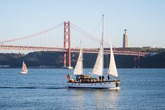 Lisbon, Portugal - 12/28/18: Sailboats on the Tagus River, 25 April Bridge background royalty free stock image