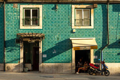 Lisbon, Portugal - Septmember 19, 2016: Tiled facade and girls drinking coffee Stock Photos
