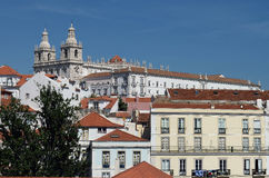 Lisbon Portugal. A view of the historic Alfama neighborhood of Lisbon Portugal  through the trees with a large majestic  cathedral on top of the hill Stock Images