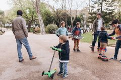 Lisbon, Portugalia 01 może 2018: Dbający ojcowie chodzą z ich dziećmi i uczą one przejażdżka jeździć na deskorolce i hulajnoga Obraz Stock