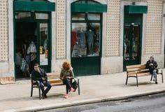 Lisbon, Portugalia 01 może 2018: ludzie siedzą na ławce z telefonami lub smartphones Sposoby komunikaci i socjalny sieci Fotografia Stock