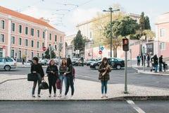 Lisbon, Portugalia 01 może 2018: Pedestrians krzyżują ulicę Dziewczyny lub firma przyjaciela stojak na skrzyżowaniu Fotografia Royalty Free