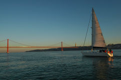 Lisbon sailing boat and 25 de Abril Bridge, Tagus river Stock Photos