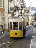 Lisbon street scene with yellow tram. The Lisbon tramway network is operation since 1873. It presently comprises five urban lines and is primarily a tourist Stock Photo