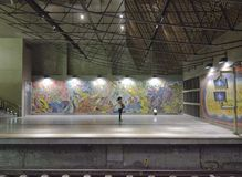 Lisbon subway station with murals and a girl speaking at the phone Stock Photos