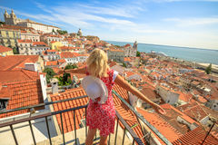 Lisbon tourist viewpoint. Lisbon aerial view of popular Church of Sao Vicente of Fora and Tagus river. Happy tourist woman with open arms admiring Alfama from royalty free stock photo