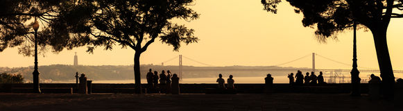 Lisbon view panorama. Beautiful panoramic image of silhouettes looking at the Ponte 25 de Abril bridge and the Sanctuary of Christ the King Cristo Rei at sunset stock image