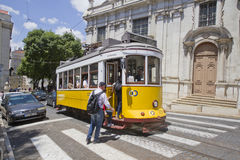 Lisbon yellow tram and passengers entering. Royalty Free Stock Photography