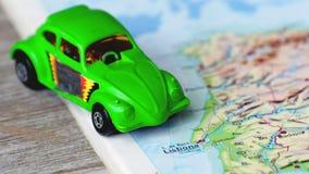 Lisborn ed il Portogallo tracciano l'automobile verde del giocattolo dello scarabeo sul fondo di legno dell'atlante archivi video