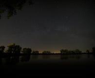 Lisci la superficie del lago della foresta su un fondo del cielo notturno a Immagini Stock