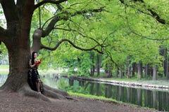 Lisez un support de livre sous un arbre de fleur images libres de droits