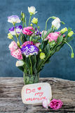 Lisianthus bouquet on a wooden table with blank note message Be Stock Photo