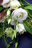 Lisianthus Flowers Bouquet. Elegant Flowers Bouquet with White Lisianthus with Buds and Decorative Green Stems closeup on Dark Grunge background. Focus on Royalty Free Stock Photo