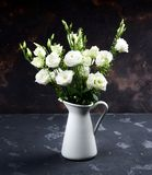 Lisianthus Flowers Bouquet. Elegant Flowers Bouquet with White Lisianthus and Decorative Green Stems in White Tin Jug closeup on Dark Grunge background Stock Photos