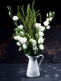 Lisianthus Flowers Bouquet. Elegant Flowers Bouquet with White Lisianthus and Decorative Green Stems in White Tin Jug closeup on Grey Grunge background Royalty Free Stock Photo