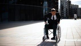 Lisie al hombre de negocios que intenta levantarse de la silla de ruedas al aire libre almacen de video