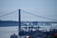 Lissabon - bro 25 avril och skeppsdocka i afton Royaltyfria Bilder
