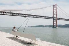 Lissabon Juni 18, 2018: En lokal fiskare fiskar på stranden i det Belem området Vanligt stadsliv och Arkivfoto