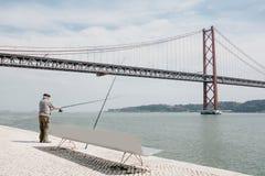 Lissabon Juni 18, 2018: En lokal fiskare fiskar på stranden i det Belem området Vanligt stadsliv och Royaltyfri Fotografi
