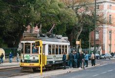 Lissabon Juni 18, 2018: Lokaler försöker att få in i den fullsatta gammalmodiga gula spårvagnen på spårvagnstoppet Det vanliga da Royaltyfri Bild
