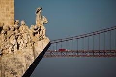 Lissabon-Monument zu den Entdeckungsforscherstatuen mit der 25. von April-Brücke Stockfotografie