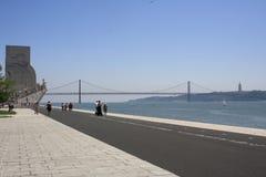 Lissabon Monumento aos Descobrimentos och bro Arkivfoto
