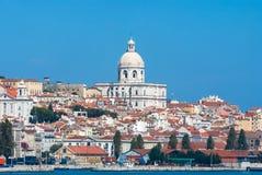 Lissabon, Portugal - April 03, 2010: stadsmening van overzees De kerkbouw en huizen op zonnige blauwe hemel Architectuur en Stock Afbeeldingen