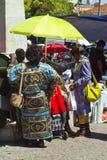 Lissabon Portugal - Maj 4, 2013 beklär två darkskinned kvinnor i traditionell vibrerande färgrik afrikan bying något in Arkivbild
