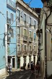 Lissabon Portugal - Maj 4, 2013 Smal gata med spårvagnstänger och blåa byggnader Arkivfoton