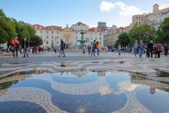 LISSABON PORTUGAL - NOVEMBER 2, 2017: Reflexioner efter regn på den lappade trottoaren på Rossio kvadrerar med en springbrunn och Arkivfoto