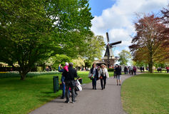 Lisse, The Netherlands - May 7, 2015: Old windmill with many tourists in famous garden in Keukenhof. Royalty Free Stock Photos