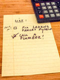 List with calculator reminding to call plumber, copy space Royalty Free Stock Photography