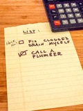 List with calculator reminding to call plumber, copy space Stock Photo