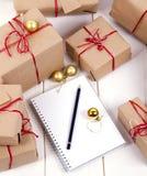List d'envie dedans au carnet près des cadeaux de Noël Photographie stock libre de droits