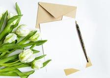 List, koperta i bukiet na białym tle, Zaproszenie karty lub list miłosny z białymi tulipanami, Odgórny widok, mieszkanie nieatuto Obraz Royalty Free
