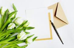 List, koperta i tulipany na białym tle, Zaproszenie karta lub list miłosny, Odgórny widok, mieszkanie nieatutowy obraz stock