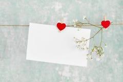 List miłosny wiesza na arkanie i kwiacie na lekkim tle Zdjęcia Stock