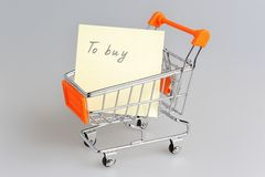 List of purchases in shopping cart on gray Royalty Free Stock Image