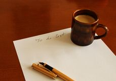 List to do. Cup of coffee and pen on wooden table Royalty Free Stock Photo