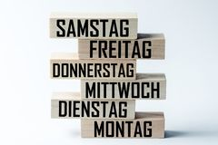 A list of wooden blocks lying on top of each other with a list of days of the six-day work week in German, in the translation of. The word: saturday, friday royalty free stock photography