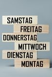 A list of wooden blocks lying on top of each other with a list of days of the six-day work week in German, in the translation of. The word: saturday, friday stock images