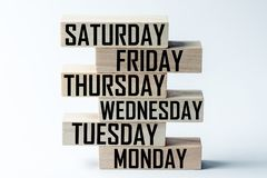 List of wooden blocks lying on top of each other with a list of days of the six-day working week in English. Horizontal frame. List of wooden blocks lying on top stock image