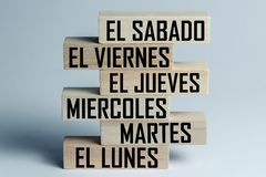 A list of wooden blocks lying on top of each other with a list of six-day working week days in Spanish, in the translation of the. Word: saturday, friday royalty free stock images