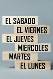 A list of wooden blocks lying on top of each other with a list of six-day working week days in Spanish, in the translation of the. Word: saturday, friday royalty free stock image
