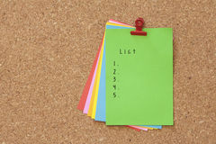 List written on color sticker notes over cork board background. List  written on color sticker notes over cork board background Royalty Free Stock Photos