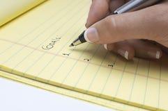 Lista da escrita da mão de objetivos no bloco de notas Foto de Stock Royalty Free