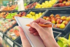 Lista de compra da escrita por Supermercado Fruta Fotos de Stock