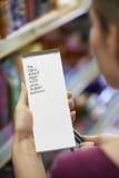 Lista de compra da leitura da mulher no supermercado fotos de stock