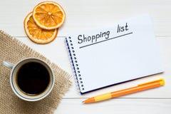 Lista de compra no bloco de notas na tabela de madeira branca, espaço da cópia para seu texto fotografia de stock royalty free