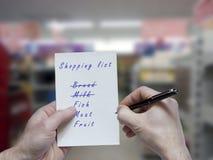 Lista de compras en la tienda Foto de archivo